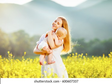 Happy family mother and baby hugging in a meadow  yellow flowers on nature in summer