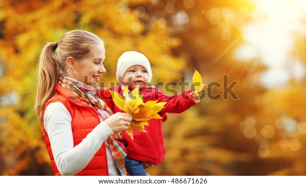 happy family mother and baby laugh with leaves in nature autumn