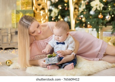 happy family mother and baby little son playing home on Christmas holidays.Toddler with mom in the festively decorated room with Christmas tree. Portrait of mother and baby boy in casual clothes.