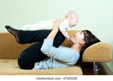 happy family: mother and baby on the sofa - playing and smiling