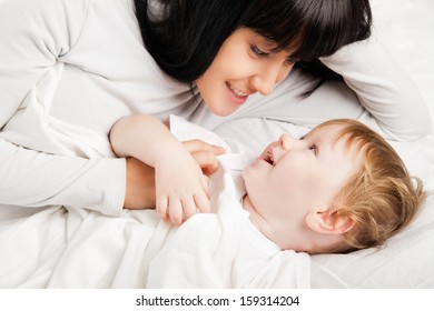happy family. Mother and baby playing and smiling in bed