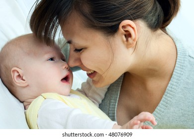 happy family: mother and baby - playing and smiling