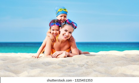 Happy family mother and chidren in masks for swimming on the beach in summer