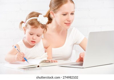 happy family mother and child baby daughter at home working on the computer