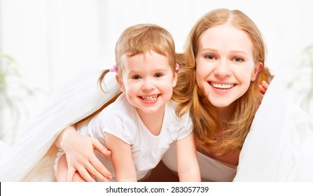 happy family mother and child baby daughter playing and having fun in bed