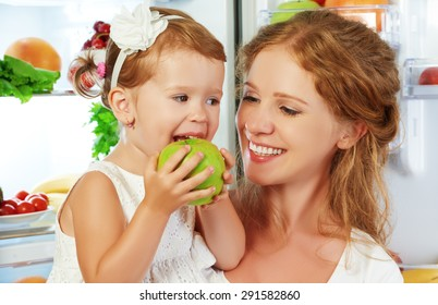 happy family mother and child baby daughter around the refrigerator with healthy food fruits and vegetables