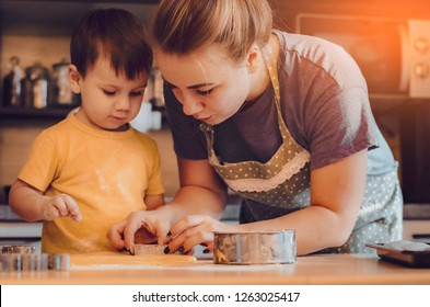 Happy family mother and child boy bake kneading dough in kitchen. Concept of family leisure in the kitchen, the child is preparing food various dishes: pasta, cookies. selective focus, noise effect