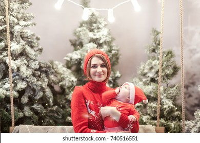 Happy family mother and child boy in santa hat near snow covered Christmas trees with sitting on swing. Bright garland above heads