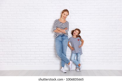 happy family mother and child daughter near an empty brick wall