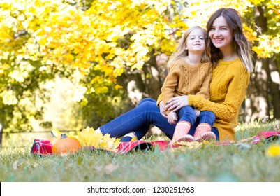 Happy family mother and child daughter playing and laughing on autumn walk. Family time together.