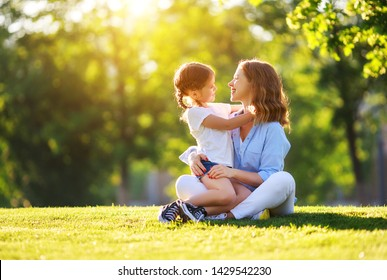 happy family mother and child daughter in nature Park in summer on green grass