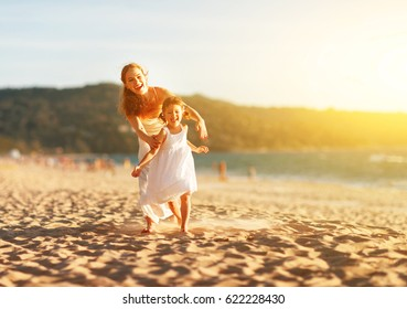 happy family  mother and child daughter run, laugh and play at beach