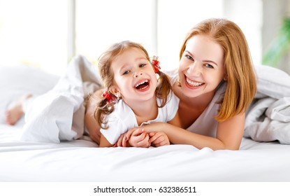 Happy family mother and child daughter play and laugh in bed
