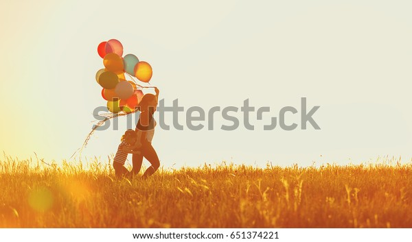 Happy family mother and child daughter running with balloons on meadow in summer at sunset