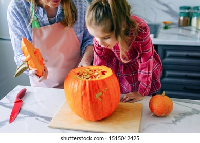 Happy family mother and child happy girl is cutting a pumpkin and is preparing for the holiday Halloween.Happy Halloween. Recipe pumpkin puree. Ingredients for pumpkin pie for Thanksgiving day.