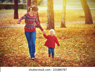 happy family mother and child little daughter running and playing on autumn walk