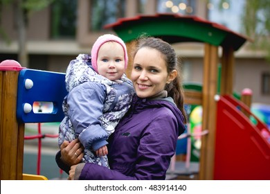 Happy family: Mother and child - little girl walking in autumn park: baby  mammy posing at playground, close up