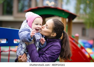 Happy family: Mother and child - little girl walking in autumn park: mammy kissing daugther posing at playground, close up