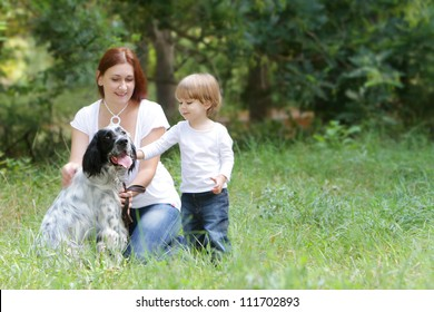 happy family - mother and child - playing with dog outdoors