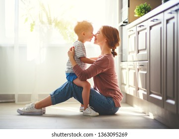 happy family mother and child son hugging in kitchen