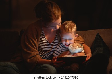 happy family mother and child son with  tablet in evening before bed
