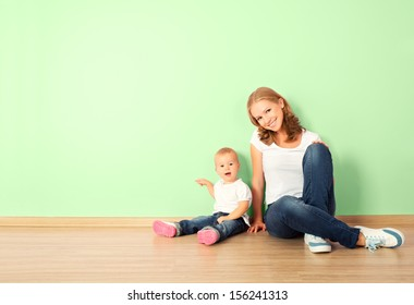 happy family of mother and child is a toddler sitting on the floor in an empty home wall in the room