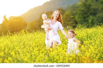 happy family, mother and children girl little daughter and baby running  on meadow with yellow flowers