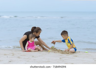 Happy family mother and children playing sand together on the beach