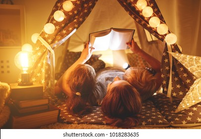happy family mother and children reading a book with a flashlight in a tent at home