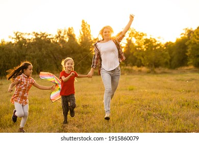 happy family mother and children run on meadow with a kite in the summer on the nature