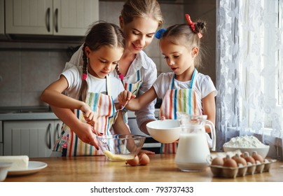Happy family mother and children twins daughter bake kneading dough in the kitchen