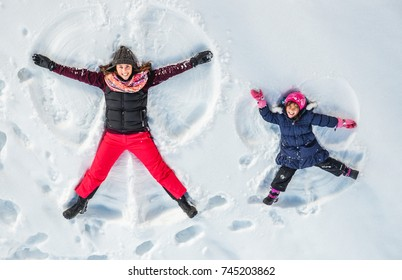 Happy family, mother and cute daughter making snow angel while lying on snow.  - Shutterstock ID 745203862