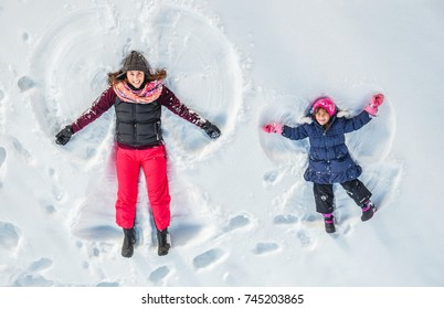 Happy family, mother and cute daughter making snow angel while lying on snow.