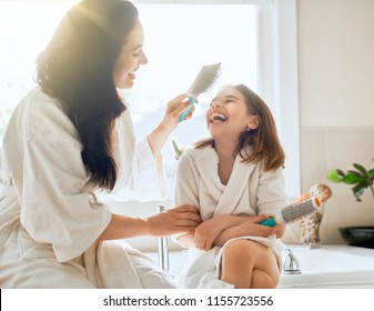 Happy family! Mother and daughter child girl are combing hair in the bathroom.