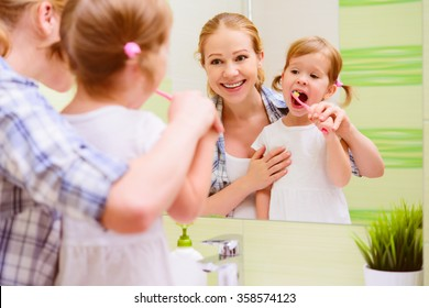 happy family mother and daughter child girl brushing her teeth toothbrushes front of the mirror in the bathroom