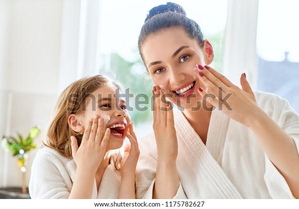 幸せな家族!母と娘の子どもがトイレで肌の世話をしている。