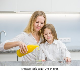 happy family - mother and daughter drinking orange juice in the kitchen