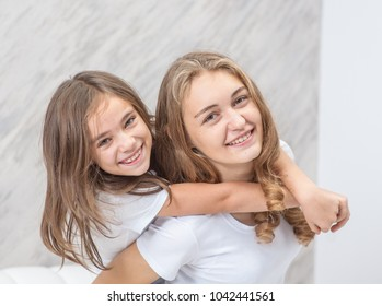Happy family - mother and daughter have fun on the bed