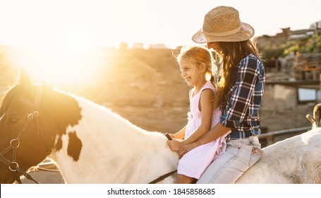 Happy family mother and daughter having fun riding horse inside ranch