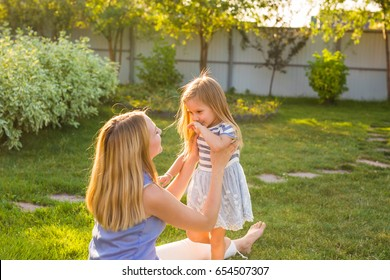 happy family mother and daughter hugging in summer on the nature