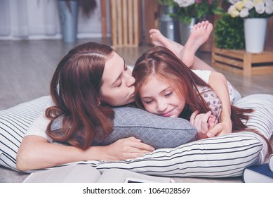 Happy family. Mother and daughter are learning to write and reading. Young beautiful mother and daughter hug, laying on the floor and reading thing. Mother teaches her lovely girls for homework.