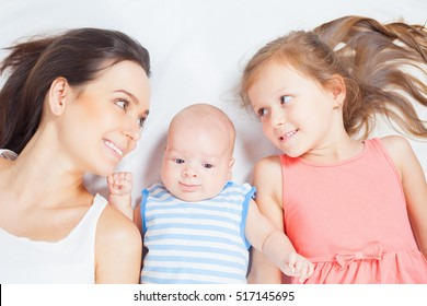 Happy family of mother with daughter looking at baby