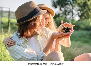 Happy family mother with daughter in nature, woman holding small newborn baby chicks in hands, farm, country rustic style, background grass garden, golden hour