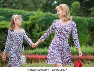 Happy family - mother and daughter - outdoors in summer day. Mother Day. Woman and child with red shopping bag having fun together during walk in the park.
