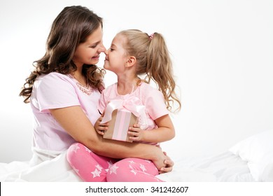 Happy family. Mother and daughter with pink gift box