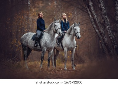 Happy family. Mother with a daughter riding horses in the forest.