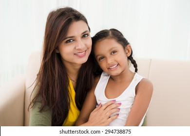 Happy family: mother and daughter sitting on the sofa at home