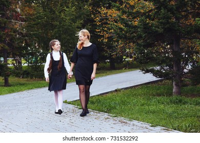 Happy family (mother with daughter) walking in golden maple autumn park