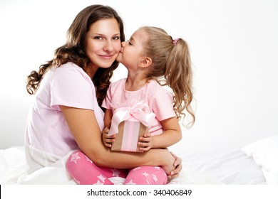 Happy family. Mother and daughters with pink gift box and flowers. Mother's day