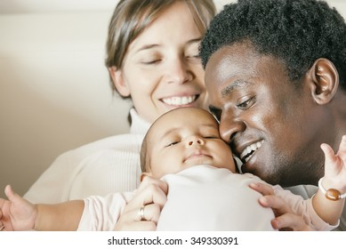 Happy Family, Mother, Father And Baby on Bed